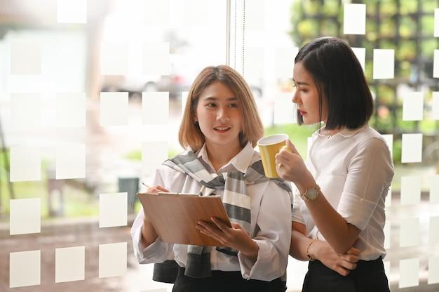 Jóvenes colegas dos mujeres reunión con lista de verificación de trabajo.
