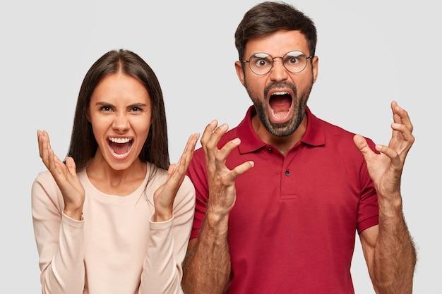 Jóvenes colegas frustrados molestos, gritan enojados, gestos activamente