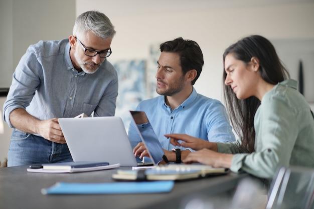 Jóvenes colegas con jefe mayor trabajando con computadoras.