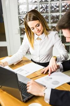 Jóvenes colegas de negocios discutiendo el trabajo en una computadora portátil en el espacio de trabajo conjunto, empresarios corporativos