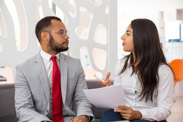 Jóvenes colegas profesionales discutiendo contrato