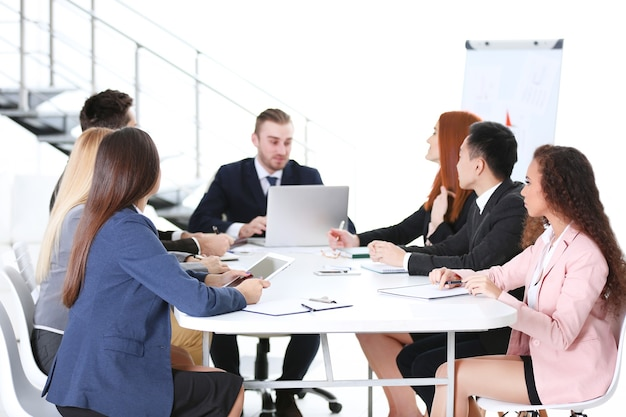 Jóvenes colegas sentados en la reunión de negocios en la oficina
