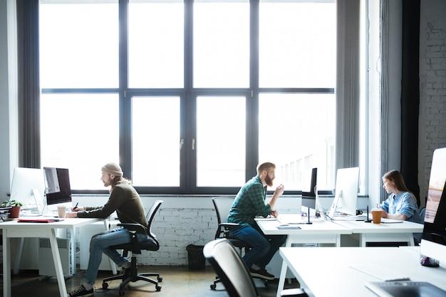 Jóvenes colegas trabajan en la oficina usando computadoras Foto gratis