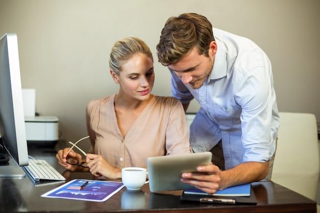 Jóvenes colegas usando tableta digital en la oficina