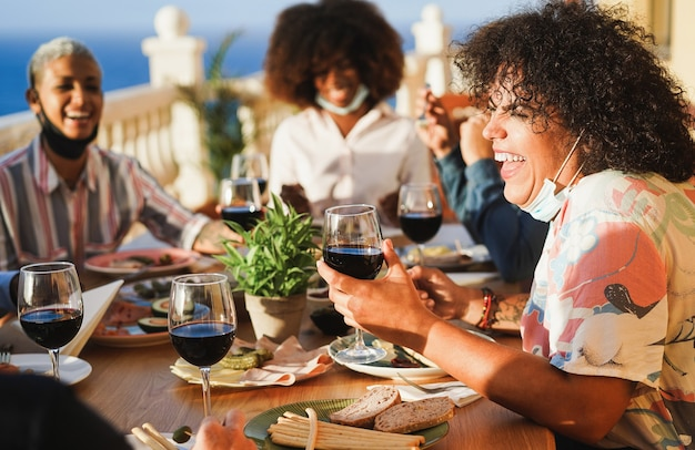 Los jóvenes comiendo y bebiendo vino tinto con máscaras protectoras