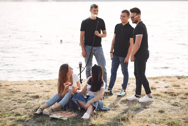 Jóvenes comiendo pizza y fumando shisha en la playa