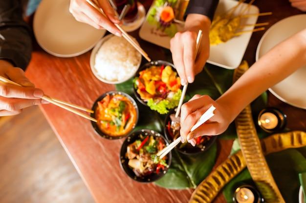 Jóvenes comiendo en restaurante tailandés