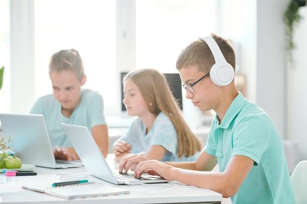 Uno de los jóvenes compañeros de clase en auriculares mirando la pantalla del portátil mientras ve videos en línea por escritorio