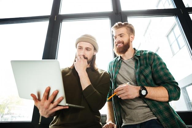 Jóvenes concentrados hombres colegas en la oficina usando laptop