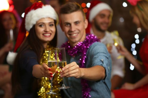 Los jóvenes con copas de champán en la fiesta de navidad, cerrar