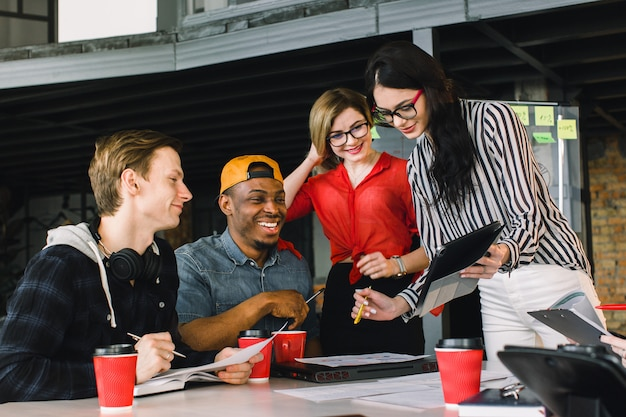 Jóvenes creativos multirraciales en la oficina moderna. grupo de jóvenes empresarios están trabajando junto con ordenador portátil, tableta, teléfono inteligente, portátil. equipo exitoso hipster en coworking.