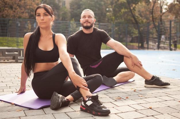 Jóvenes deportistas en colchoneta haciendo posición de yoga
