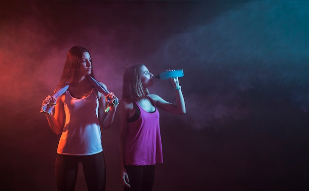 Jóvenes deportistas descansando en estudio oscuro
