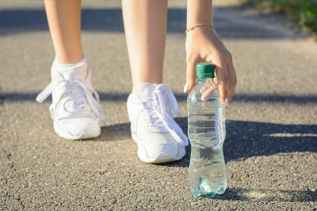 Los jóvenes deportistas de zapatillas blancas se detuvieron en el camino para hacer una pausa y beber agua