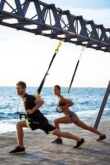 Jóvenes deportivos entrenando con trx cerca del mar en la mañana.