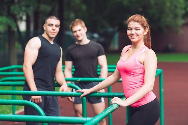Los jóvenes descansan después de hacer ejercicio en la cancha deportiva.
