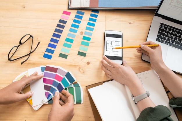 Una de las jóvenes diseñadoras apuntando al boceto de la casa en el teléfono inteligente mientras consulta con un colega sobre algunos puntos del proyecto
