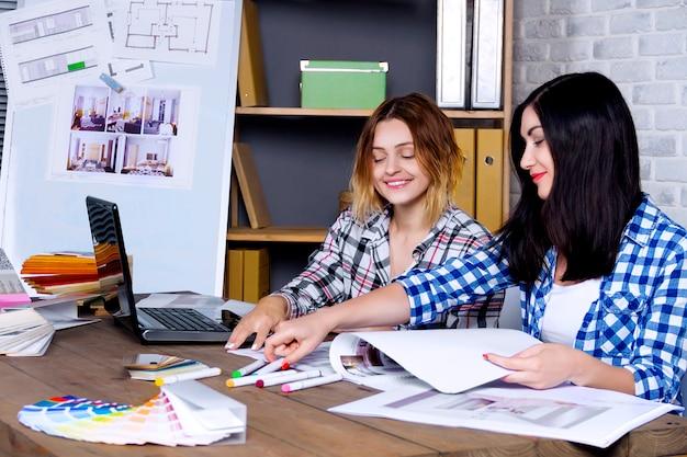 Jóvenes diseñadores de interiores independientes que trabajan desarrollan un nuevo proyecto de apartamento en un estudio de diseño. dos mujeres, niñas, mujeres, reuniones con un escritorio con pin up, bocetos, dibujos y borradores del nuevo proyecto