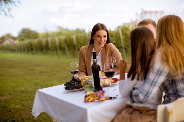 Los jóvenes disfrutan de una cena y cata de vinos en el viñedo.