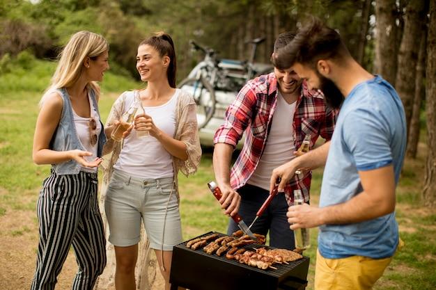 Jóvenes disfrutando de la fiesta de la barbacoa en la naturaleza.