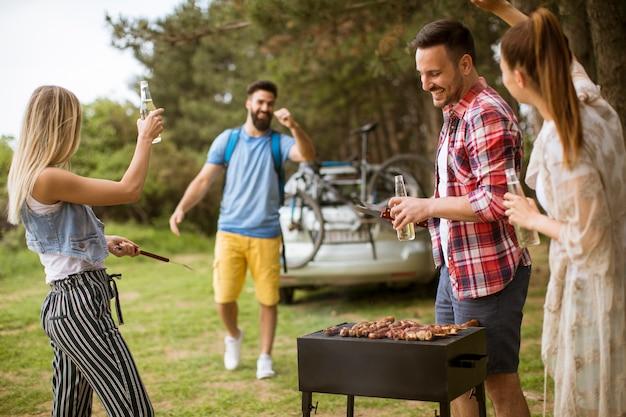 Jóvenes disfrutando de la fiesta de barbacoa en la naturaleza.