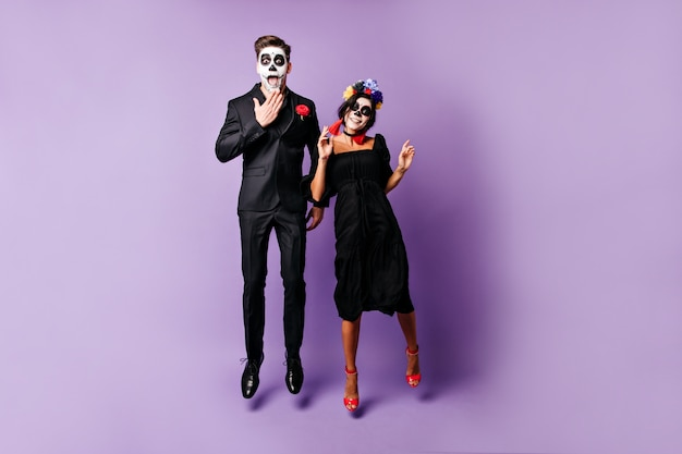 Jóvenes divertidos con arte facial en halloween posan emocionalmente, saltando sobre fondo púrpura.