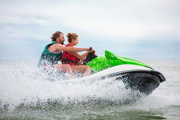 Los jóvenes se divierten conduciendo a alta velocidad en motos de agua, hombre y mujer en vacaciones de verano, amigos haciendo deporte activo