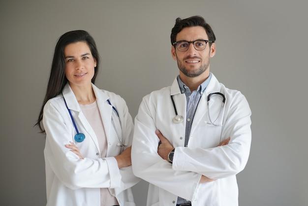 Jóvenes doctores en bata de laboratorio sonriendo