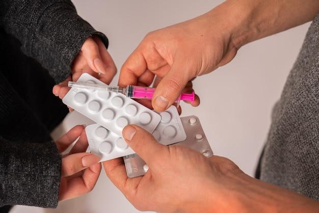 Los jóvenes con drogas y jeringas en sus manos, estudio de cerca photo