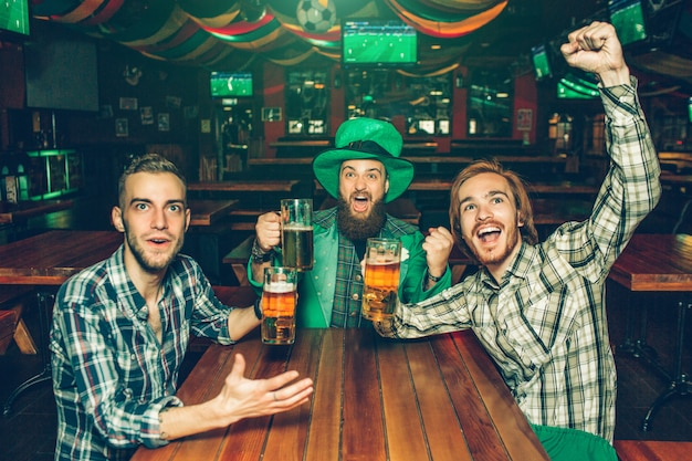 Los jóvenes emocionados se sientan a la mesa en el pub y miran hacia adelante. ellos animan los hombres sostienen jarras de cerveza en las manos. hombre joven en medio llevar traje verde de san patricio.