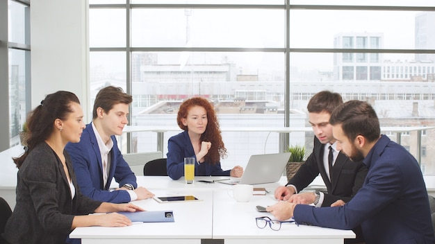 Jóvenes empleados de oficina de una empresa que comparte una mesa.