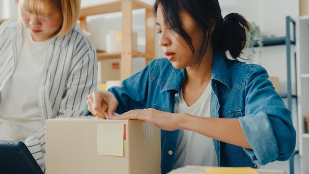 Jóvenes empresarias asiáticas que usan el teléfono móvil que reciben la orden de compra y verifican el producto en el trabajo de stock en la oficina en casa
