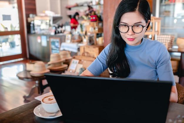 Las jóvenes empresarias se centran en la escritura de cuadernos mientras aprenden y trabajan en cafeterías