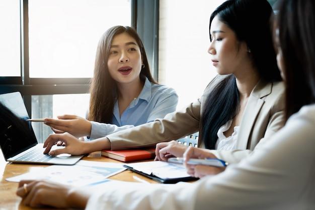 Jóvenes empresarias discuten la estrategia de gráficos y plan financiero.