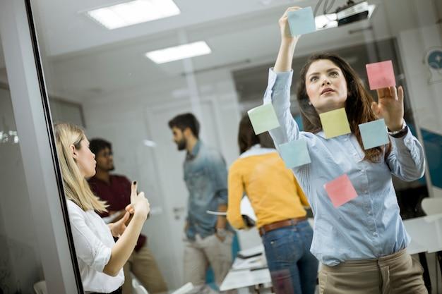 Jóvenes empresarias discutiendo frente a la pared de vidrio usando notas y pegatinas