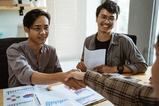 Jóvenes empresarios asiáticos estrecharon sus manos de acuerdo