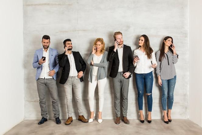Jóvenes empresarios con teléfono móvil de pie junto a la pared