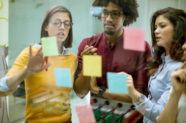 Jóvenes empresarios discutiendo frente a la pared de vidrio usando notas y calcomanías