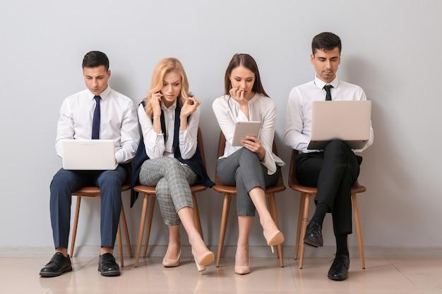 Jóvenes empresarios esperando en línea cerca de la pared de luz