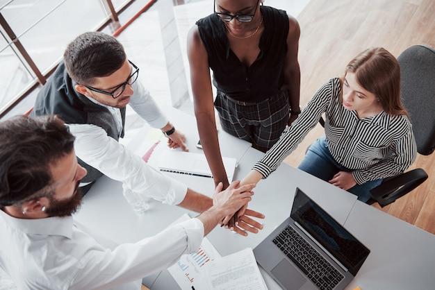Jóvenes empresarios están discutiendo nuevas ideas creativas juntos durante una reunión en la oficina