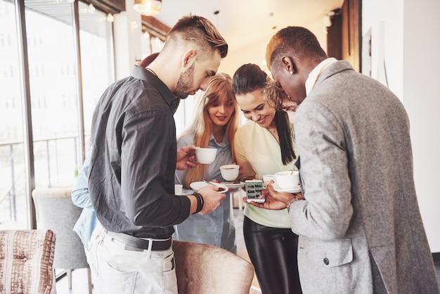 Jóvenes empresarios exitosos están hablando y sonriendo durante el descanso para tomar café en la oficina