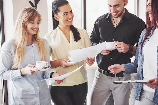 Jóvenes empresarios exitosos están hablando y sonriendo durante la pausa para el café