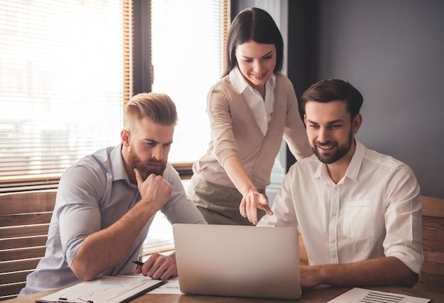 Jóvenes empresarios exitosos están utilizando una computadora portátil.