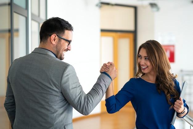 Jóvenes empresarios exitosos saludando en la oficina de la empresa