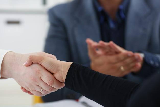 Jóvenes empresarios felices reunidos en la oficina se dan la mano