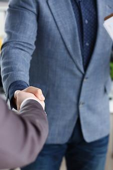 Jóvenes empresarios felices tienen reunión en la oficina se dan la mano entre sí closeup