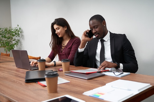 Jóvenes empresarios felices trabajando juntos en la oficina moderna, trabajo en equipo multiétnico. hombre llamando con teléfono inteligente