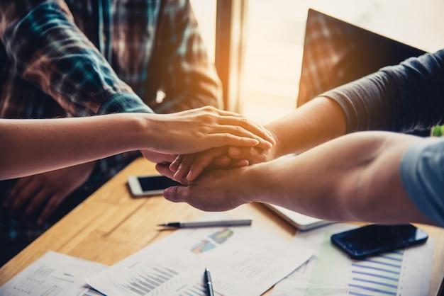 Jóvenes empresarios juntando sus manos. pila de manos trabajo en equipo