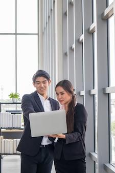 Jóvenes empresarios y mujeres de negocios asiáticos consultan juntos el trabajo.