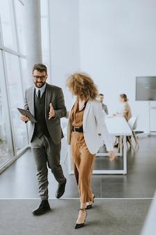 Jóvenes empresarios multiétnicos caminando juntos y hablando en la oficina moderna
